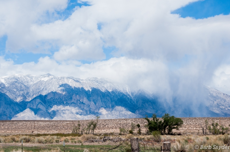 Snow coming down on the mountains ahead.