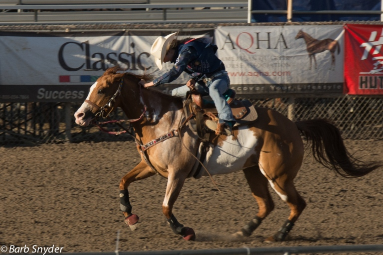 A barrel racer headed home - she's barely in the saddle.